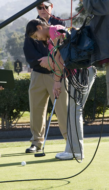 Young woman golfer putting, with Bill Cole and camera equipment